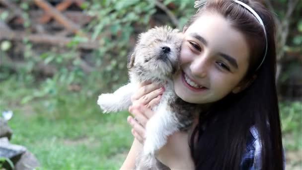 Dívka, mazlení štěně venku v zahradě