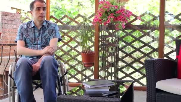 Mladý muž ve vozíku smutno