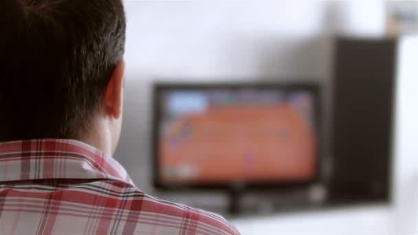 Muž sledují televizi v obývacím pokoji