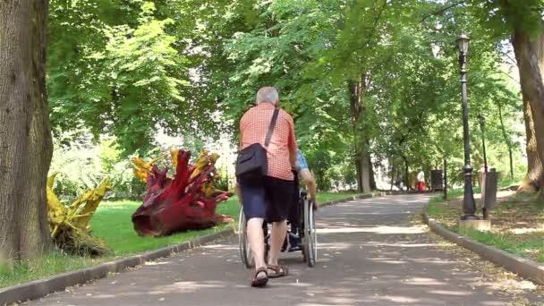 Senior geht mit behindertem jungen Mann spazieren