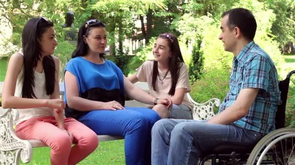 Mladý muž na invalidním vozíku s rodinou v parku