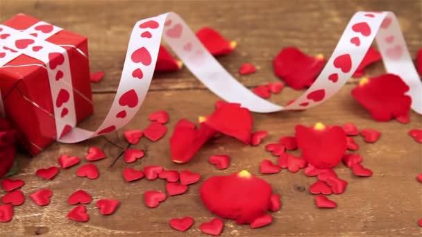 Červené růže a krabičky na dřevěné pozadí