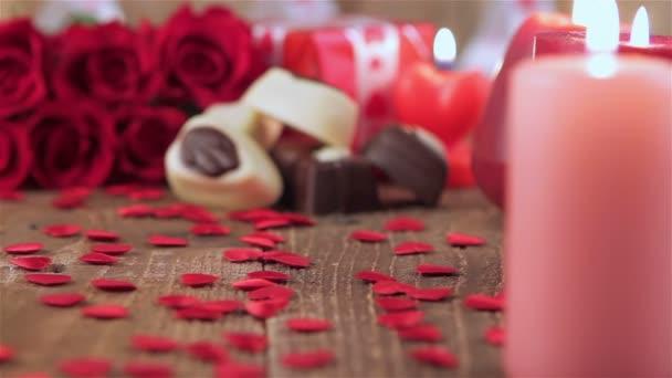 Vörös rózsa és csokoládé cukorka a gyertyák, a fa