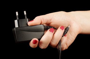 Female hand holding AC charger adapter