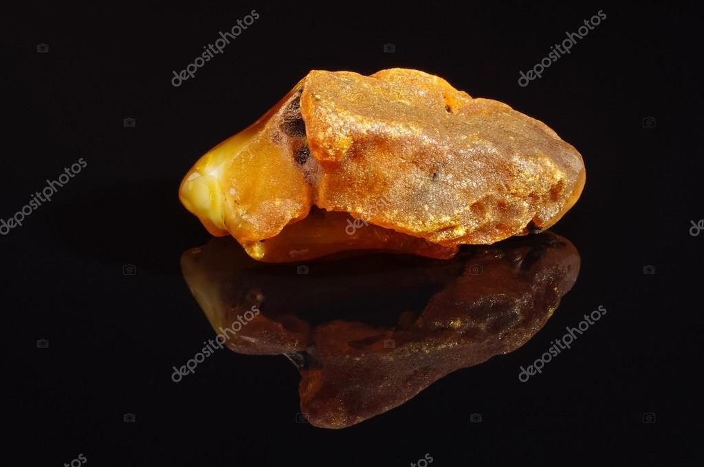 Big piece of amber on the black reflective surface