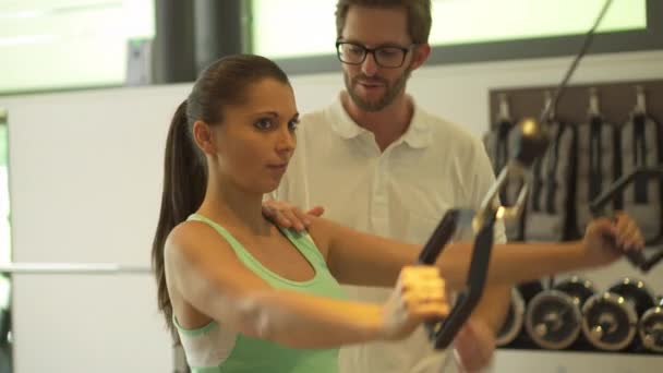 fitness trenér pomáhá žena v tělocvičně