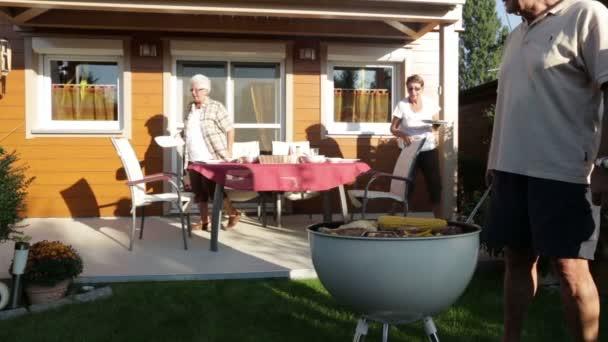 čtyři senioři s grilování v zahradě