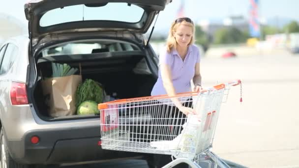 pregnant woman putting things into car