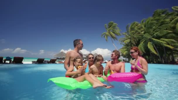family with cocktails in tropical pool
