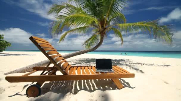 notebook on sunchair on beach