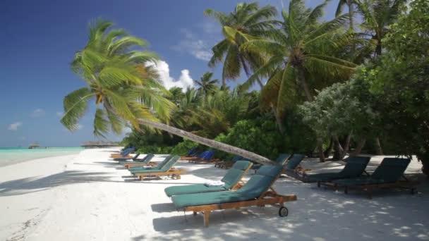 Sun lounger on white sandy beach