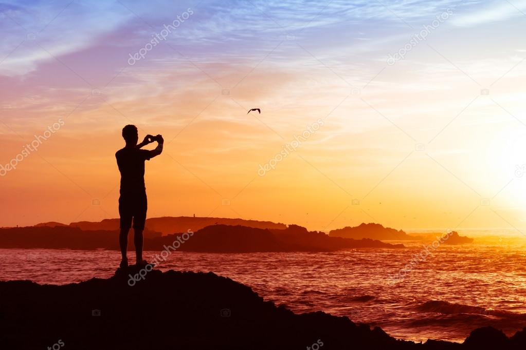Man taking photos of sunset