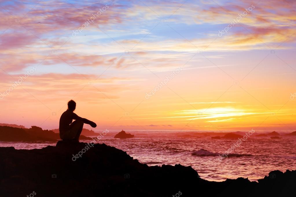 Woman sitting alone at sunset