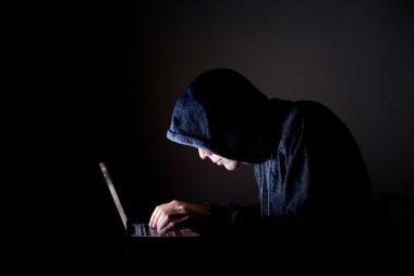 Hacker with laptop in dark