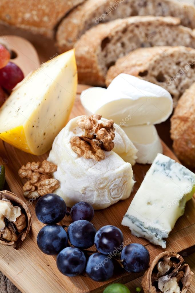 Cheese platter variety of cheeses on wooden plate with fruits and bread u2014 Photo by nschatzi & Cheese platter: variety of cheeses on wooden plate with fruits and ...