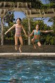 Dvě dívky, skákat do bazénu