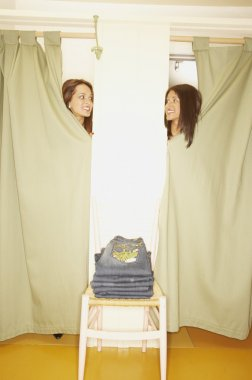Two women peeking out from two fitting rooms