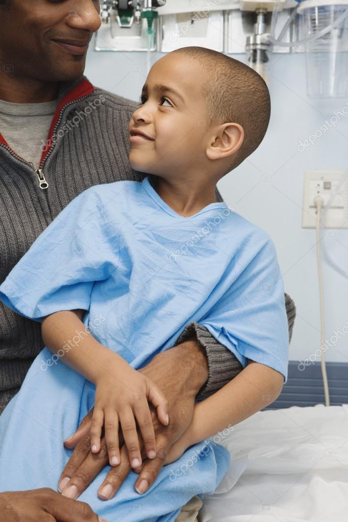 African boy in hospital gown sitting on father's lap