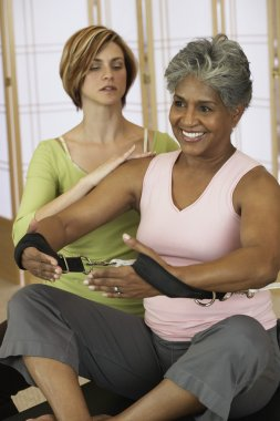 African woman exercising with personal trainer