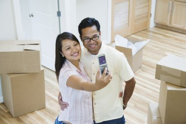 Asian couple taking own photograph in new house