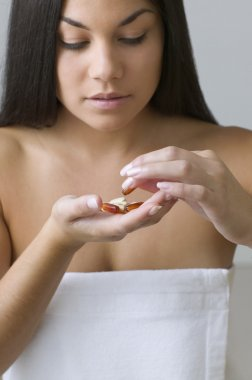 Young woman sorting out handful of pills