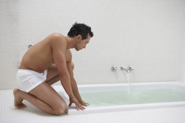 Man wearing underwear with hand in bath water