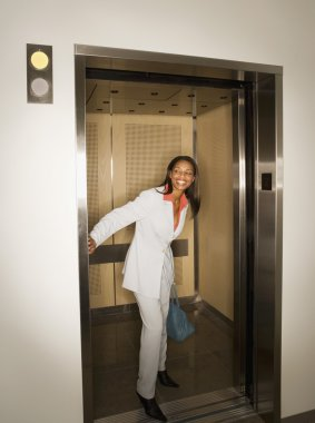 African woman holding elevator open