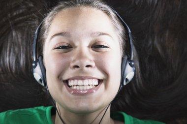 Teenage girl wearing headphones smiling