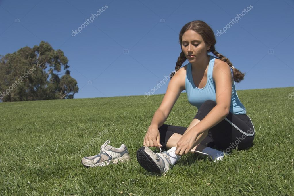 Young woman putting on athletic shoes in field