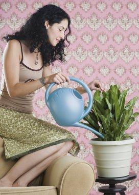 Young woman watering house plant