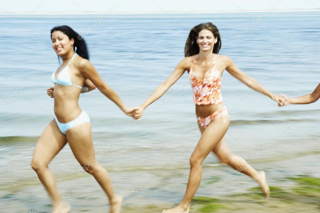 Women holding hands and running at beach