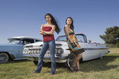 Multi-ethnic women leaning on low rider car