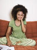 Africká žena sedí v posteli