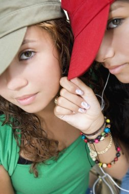 Hispanic teenaged girls wearing hats
