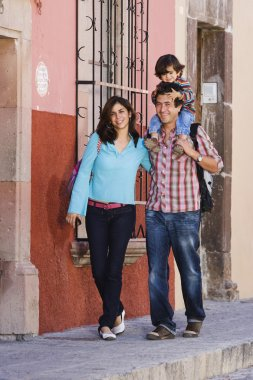 Hispanic family walking on sidewalk