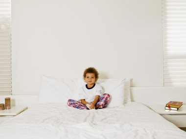 Mixed Race boy sitting on bed