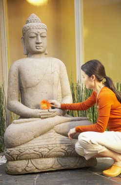 Asian woman placing flower on Buddha statue