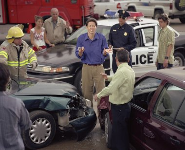 Hispanic man shrugging shoulders in middle of accident scene