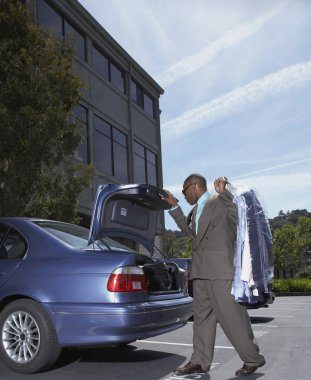 African businessman holding dry cleaning