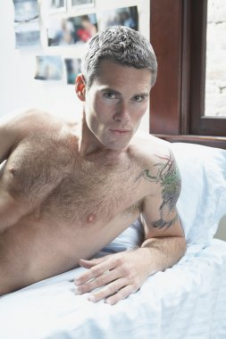 Bare-chested man laying in bed