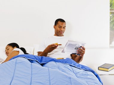 African man reading next to sleeping wife