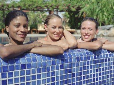 Hispanic women leaning on edge of swimming pool
