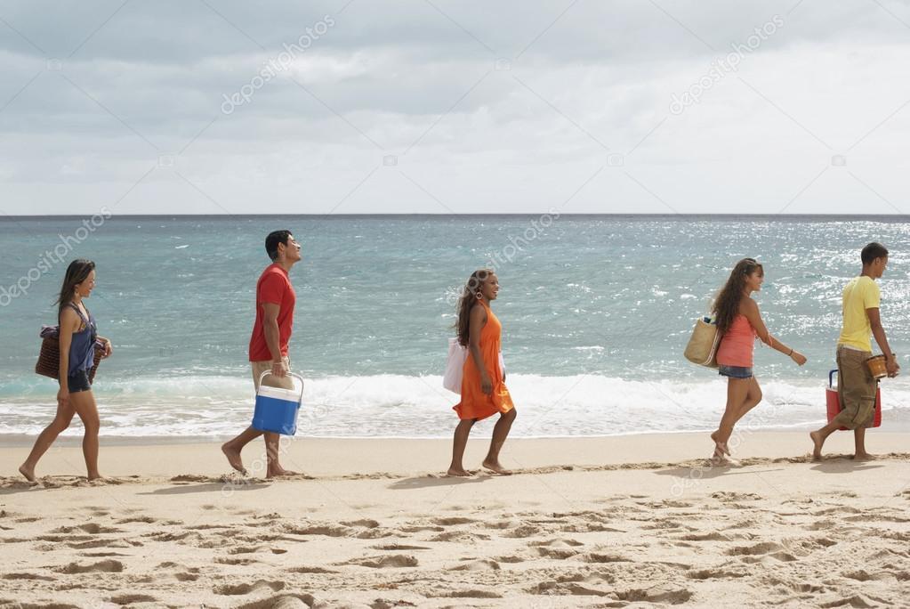 Multi-ethnic friends walking on beach