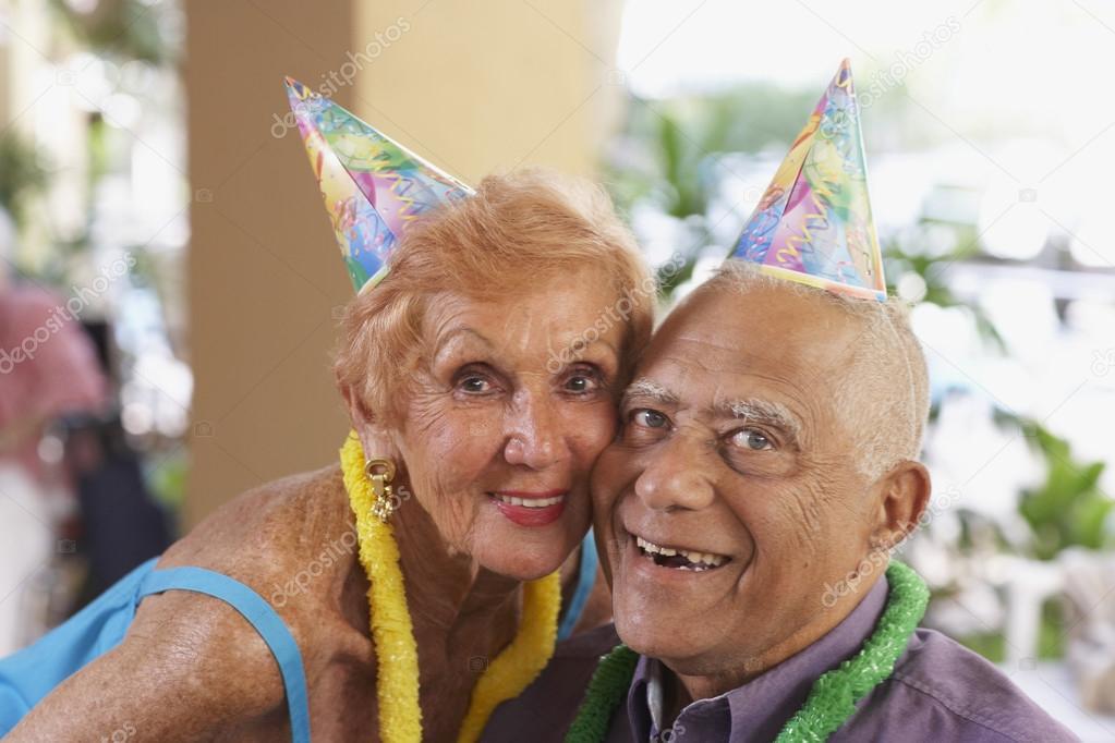 Multi-ethnic senior couple wearing party hats