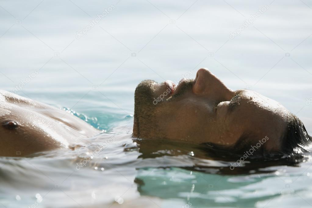 South American man floating in water