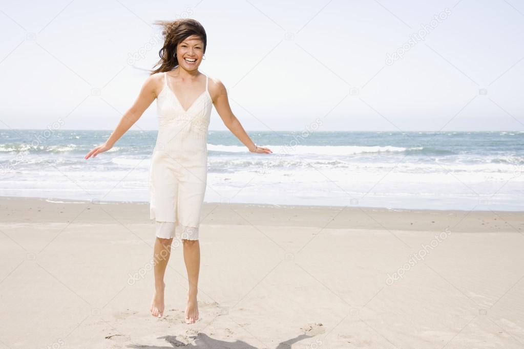 Asian woman jumping on beach