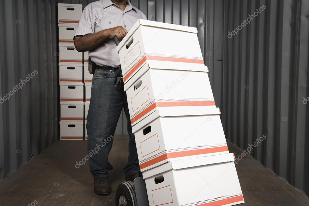 Male worker with stacks of boxes