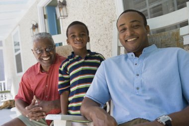 African American grandfather, father and son on porch