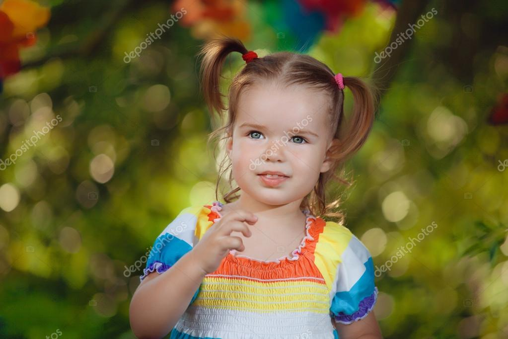 cute little girl wearing colorful dress sucks her thumb