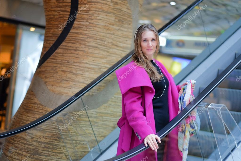 Gorgeous mature blonde woman wearing pink woolen coat in the mall — Photo  by ...